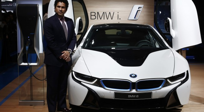 Retired cricketer Tendulkar poses with BMW's i8 hybrid car during its launch at the Indian Auto Expo in Greater Noida