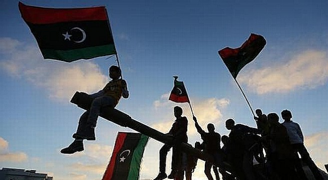 Boys carrying flags sit on a tank in Benghazi  during the third anniversary of an attack by pro-Gaddafi forces on Benghazi
