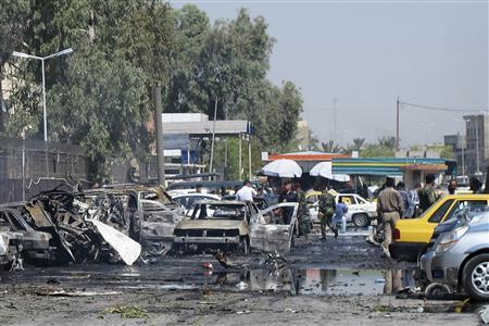 Iraqi security forces inspect damaged vehicles after a bomb attack in Baghdad's Kadhimiya district