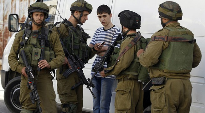 Israeli soldiers search a Palestinian youth during an operation to locate three Israeli teens in the West Bank city of Hebron