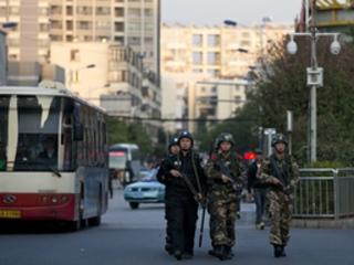 Armed policemen and paramilitary policemen patrol a street near Kunming railway station