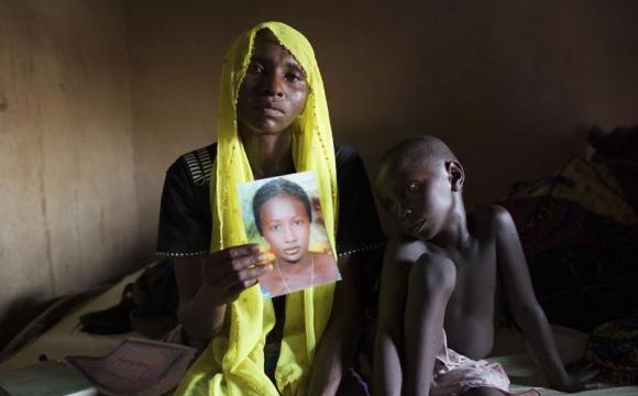 Rachel Daniel holds up a picture of her abducted daughter Rose Daniel, as her son Bukar, sits beside her at her home in Maiduguri