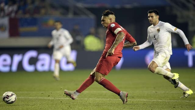 Peru's forward Paolo Guerrero (L) scores his third goal against Bolivia during their 2015 Copa America football championship quarter-final match, in Temuco, Chile, on June 25, 2015.   AFP PHOTO / JUAN MABROMATA