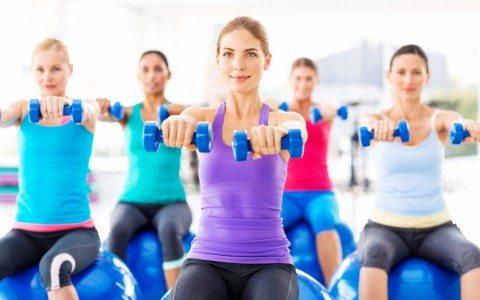 Group of young women exercising with weights while sitting on fitness ball in health club. Horizontal shot.