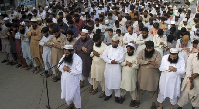 """Supporters of a Pakistani religious group, """"Jamaat-ud-Dawa,"""" offer funeral prayers for Taliban leader Mullah Mohammad Omar outside a mosque in Karachi, Pakistan, Sunday, Aug. 2, 2015. Afghanistan's Taliban on Thursday confirmed the death of Mullah Omar, who led the group's self-styled Islamic emirate in the 1990s, sheltered al-Qaida through the 9/11 attacks and led a 14-year insurgency against U.S. and NATO troops. (AP Photo/Fareed Khan)"""