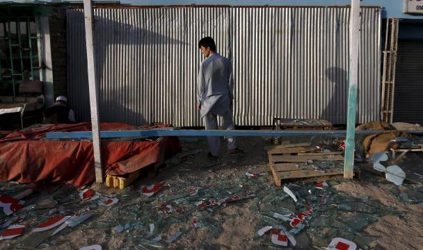 An Afghan man stands outside his damaged shop near the site of an attack after a overnight battle outside a base in Kabul, Afghanistan August 8, 2015. REUTERS/Mohammad Ismail