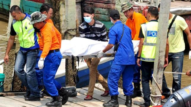 Rescuers carry a body recovered from a capsized boat believed to be carrying illegal migrants, at a jetty in Hutan Melintang, near Teluk Intan, Malaysia September 3, 2015. REUTERS/ The New Straits Times Press/S. Ravale