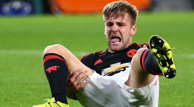 Manchester United's Luke Shaw grimaces after being injured during the Champions League Group B soccer match between PSV and Manchester United at Philips stadium in Eindhoven, Netherlands, Tuesday, Sept. 15, 2015. (AP Photo/Peter Dejong)