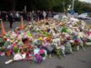 People gather next to floral tributes in Christchurch on March 17, 2019 two days after a shooting incident at two mosques in the city. - New Zealanders flocked to memorial sites to lay flowers and mourn the victims of the twin mosque massacres on March 17, as testimony emerged of epic heroism and harrowing suffering in the gun attack that has claimed 50 lives. (Photo by Marty MELVILLE / AFP)